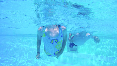 Underwater footage of two kids swimming and diving in a swimming pool Filmmaterial