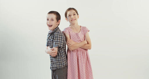 Boy and girl laughing together on white background Footage