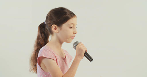 young girl singing with a microphone on white background Stock Video Footage