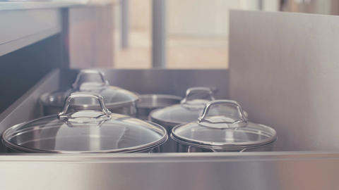 Drawer with stainless steel pots in a luxury kitchen Footage