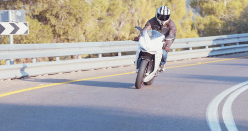 Man riding a white sport motorcycle at high speed on curved road ビデオ