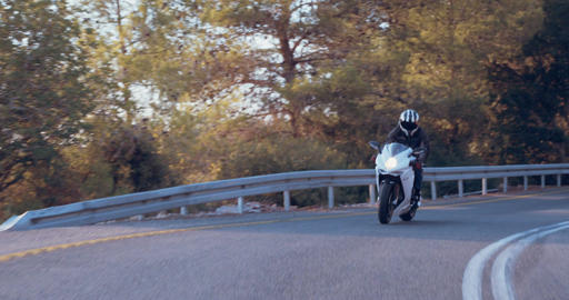 Man riding a white sport motorcycle at high speed on curved road Live Action