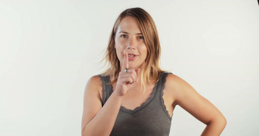 Young beautiful blonde woman saying shhh to the camera on white studio backgroun