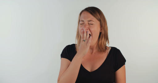 Young blonde woman yawning on a white background Footage