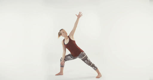 Blond woman exercising yoga routines on a white background Footage