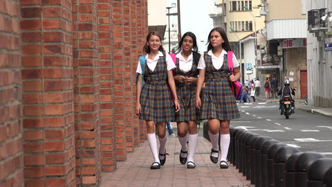 Female Students Walking On Sidewalk
