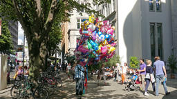 Man with bunch of balloons on alte potsdamer street in Berlin Footage