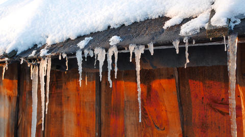 Icicles on the roof of an old barn. Slider Footage