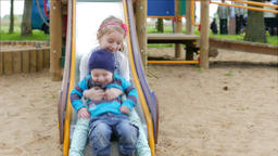 Girl and her younger brother are sliding down on slide Footage