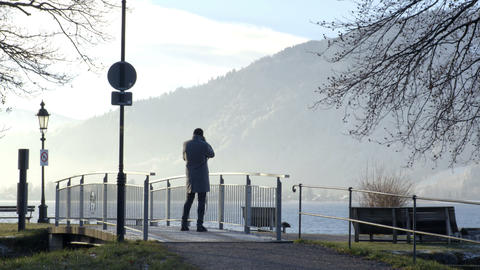 Man takes picture of nature landscape on footbridge Footage