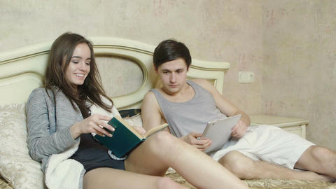 Two young people reading a book, working with a digital tablet Footage