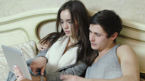 Young couple choosing what to buy on the internet using a digital tablet GIF