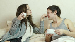 Young girl flirts, grabs the nose of Man, drink tea (coffee) GIF