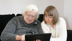 Old woman is learning how to use tablet computer Footage