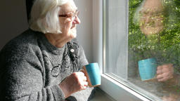 Happy old woman with a cup of tea is looking through the window in a sunny day Footage