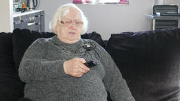Unhappy old woman is sitting on a sofa and changing channels on TV Footage