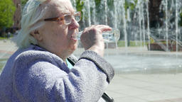 Senior woman drinks water at hot summer day Footage