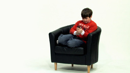 Boy fiddling on black couch HD Footage