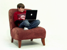 Child on couch with laptop 486p Footage