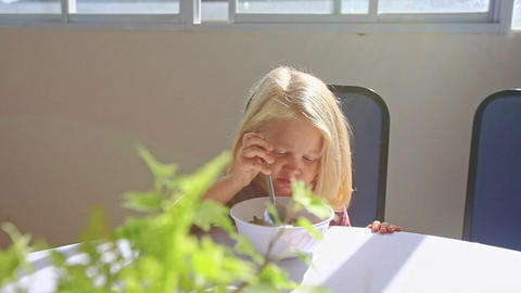 Blond Little Girl Sits at Table Eats Breakfast from Bowl Footage