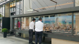 Two men are watching shopwindow with luxurious watches in Vienna Footage