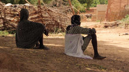 Medium shot of two tuareg women resting in traditional village Footage