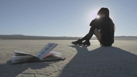 Girl sitting on the ground in the desert. Open book on foreground. Sun back ligh Footage