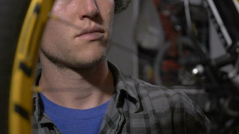 A millennial bicycle mechanic makes adjustments to a mountain bike, close up, sh