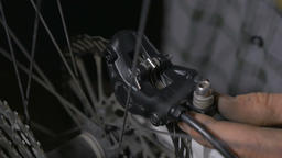 Push in of a bicycle mechanic adjusting disc brakes with greasy hands Live Action