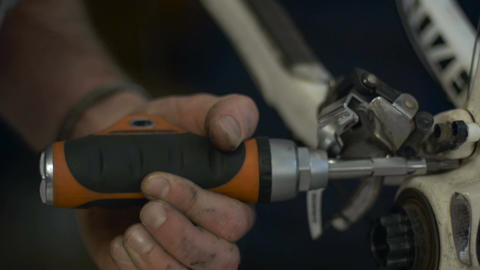 A man disassembles a rear derailleur on a bicycle with a screwdriver. The screw Live Action