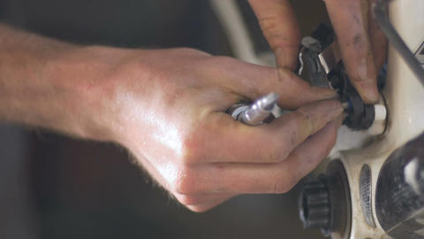 A man re-attaches a rear derailleur on a bike with a screw, then the screwdriver