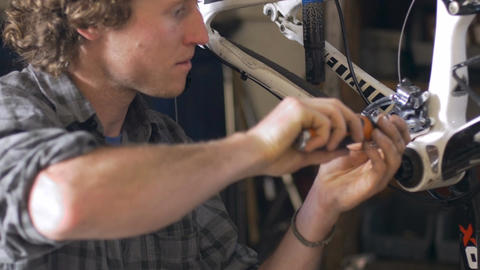 A millennial man bike mechanic assembles a mountain bike in his workshop - dolly Footage