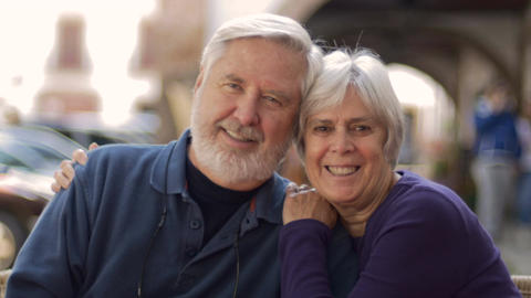A happy senior couple hugs and smiles at the camera at an outdoor cafe. They are Footage