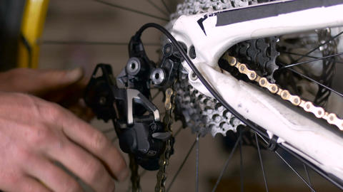 A bike mechanic threads a bicycle chain through a derailleur with his greasy, di Live Action