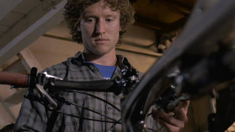 Low angle of a millennial man bike mechanic adjusting cables and shifters Footage