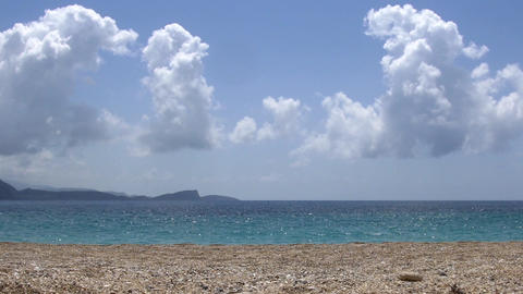 Rocky sand and clear blue sea water and fluffy clouds that reflect the blue sky  Live Action