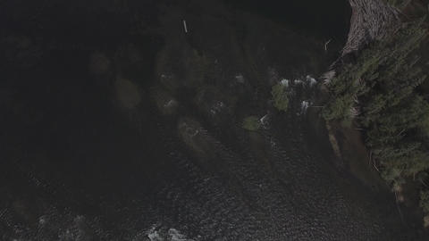Top down aerial view from a waterfall to a small dock Footage