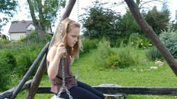 Pensive young girl on a swing Footage