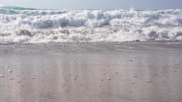 Moderate waves rolling towards a sandy beach Footage