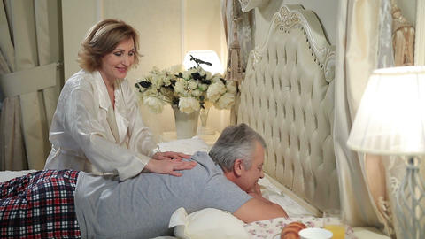 Mature woman giving massage to senior man in bed Footage