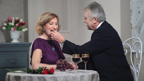 Mature woman feeding man with grapes at restaurant Footage