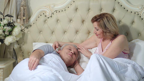 Woman gently waking up man in the morning Footage