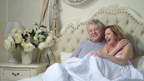 Excited senior couple laughing together in bed Footage