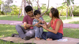 Young Asian Family Teaching Son to Read in Park - Dolly Reveal Footage