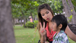 Asian Mother and Son Talking while in a Park - Dolly Tracking Shot Footage