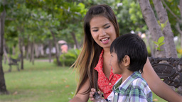 Asian Mother and Son Talking while in a Park - Dolly... Stock Video Footage