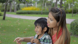 Asian Mother and Son Spending Time Together in a Park - Dolly Shot Footage