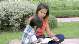Asian Mother Teaching Her Son To Read - Dolly Shot Footage