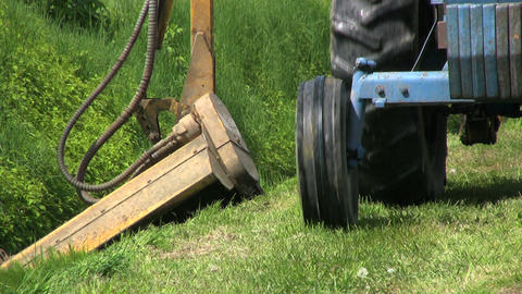 Tractor Cutting Grass In Ditch Close Up stock footage
