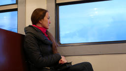Adult woman travel alone at suburban train, sit and look out window Footage